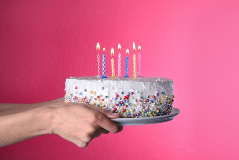 Torta di compleanno della tenuta della donna con le candele brucianti su fondo rosa immagini stock libere da diritti