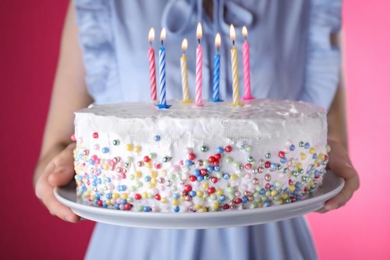 Torta di compleanno della tenuta della donna con le candele brucianti su fondo rosa fotografia stock libera da diritti