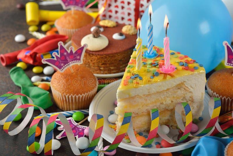 Torta di compleanno e vari accessori per la festa immagine stock