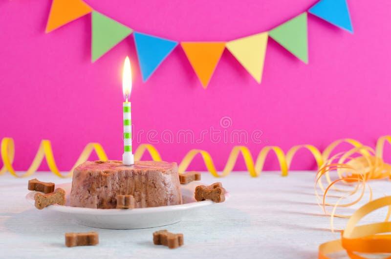 Torta di compleanno felice per il cane da alimento e dagli ossequi bagnati con la candela e sul fondo rosa del partito fotografie stock libere da diritti