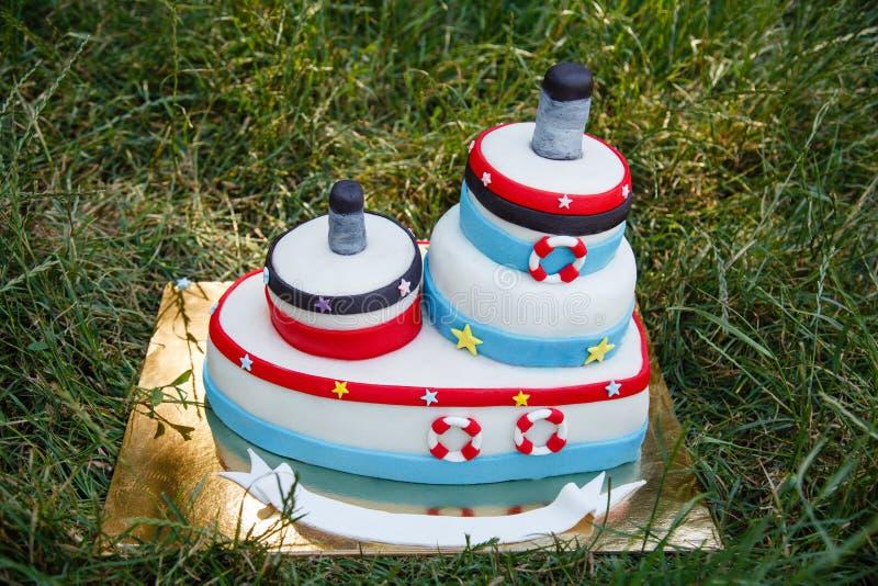Torta di compleanno nello stile marino in erba immagine stock