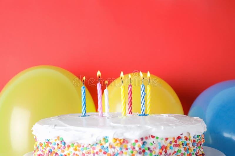 Torta di compleanno saporita con le candele brucianti ed i palloni su fondo rosso fotografie stock