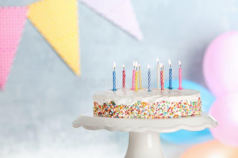 Torta di compleanno saporita con le candele brucianti sul supporto contro fondo vago fotografie stock libere da diritti