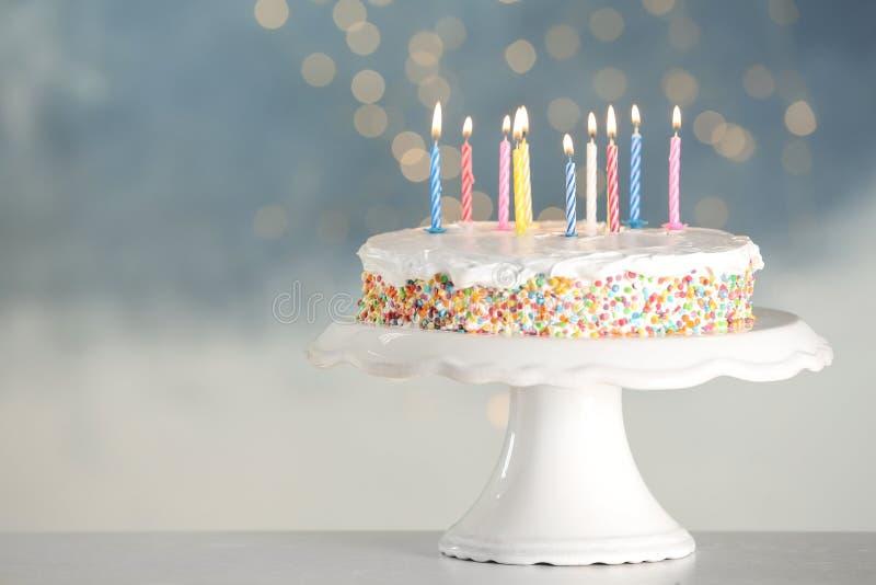 Torta di compleanno saporita con le candele brucianti sulla tavola contro le luci vaghe immagine stock libera da diritti