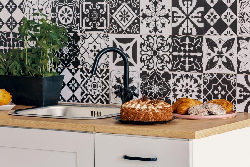 Torta di compleanno sul contatore di cucina nell'interno elegante con la parete in bianco e nero fotografia stock