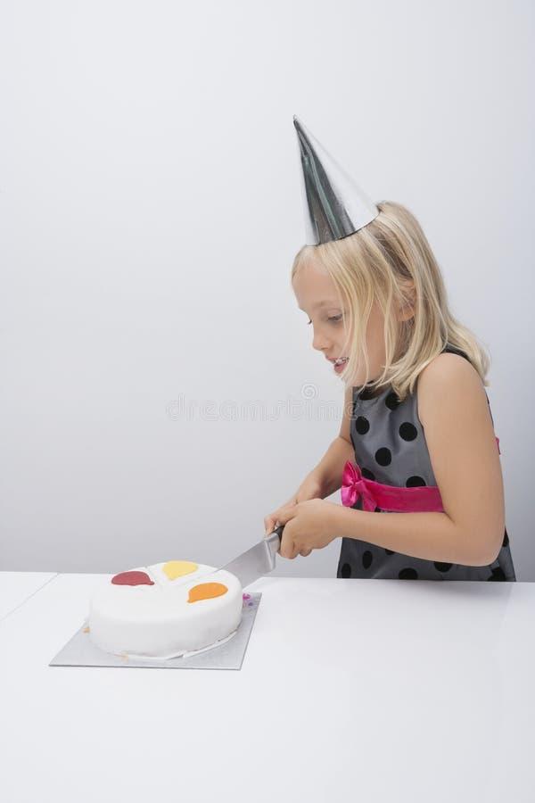 Torta di compleanno sveglia di taglio della ragazza alla tavola in casa fotografia stock - Alla tavola della longevita ...