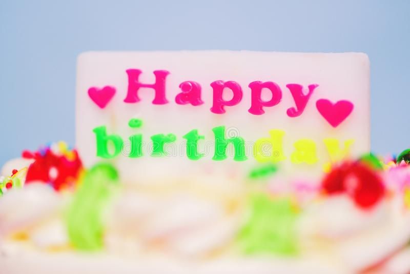 Torta di compleanno variopinta con l'etichetta di buon compleanno e di cuore a forma di vicino su fotografia stock