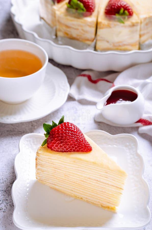 Torta di crepe con salsa di fragole servita con tè fotografia stock libera da diritti