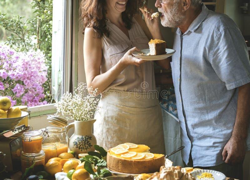 Torta di formaggio adorabile di cottura delle coppie nella cucina fotografia stock libera da diritti
