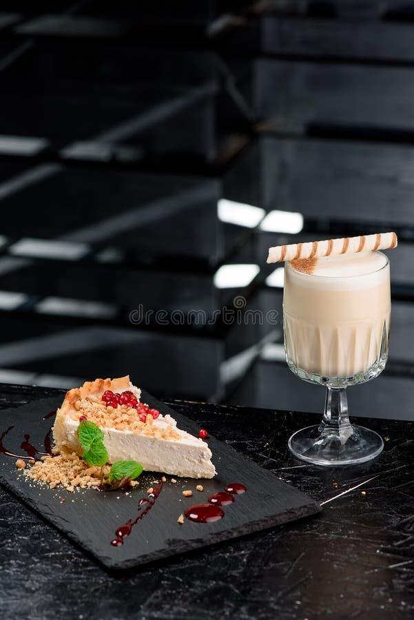 Torta di formaggio con le bacche e cappuccino o latte in un bello vetro sulla gamba contro un bello fondo scuro fotografia stock