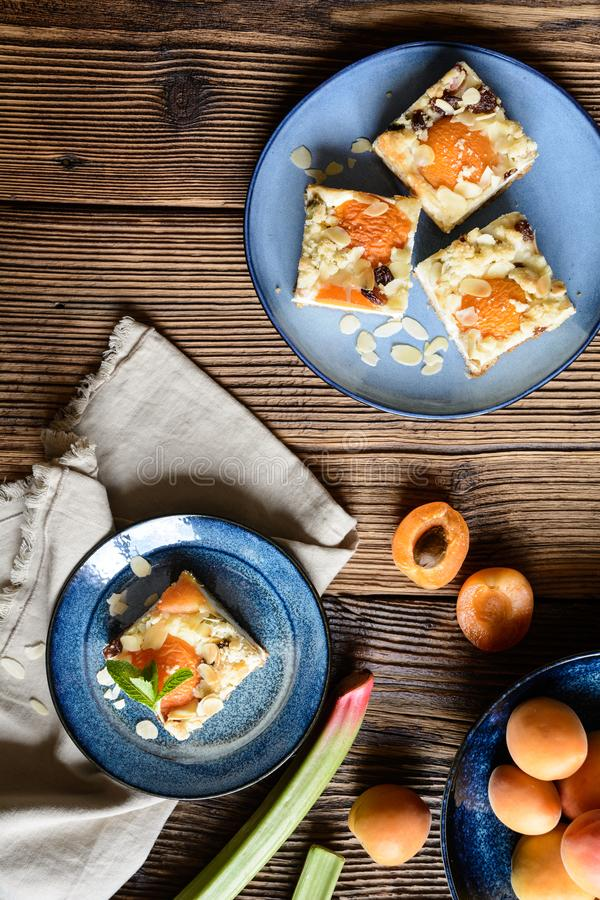 Torta di formaggio dell'albicocca con rabarbaro, completato con i fiocchi della mandorla e della briciola fotografie stock