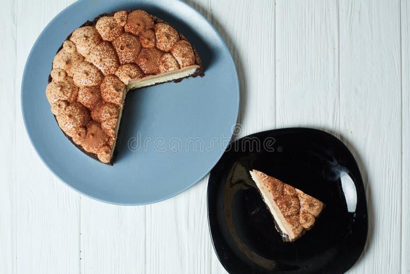 Torta di formaggio della vaniglia con la crema ed il cacao del cioccolato al latte fotografia stock libera da diritti