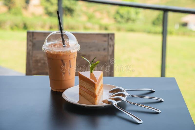 Torta di formaggio tailandese arancio del tè con la bevanda tailandese del tè del ghiaccio sulla tavola di legno in piantagione immagini stock