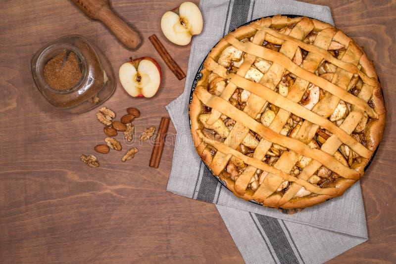 Torta di mele americana classica al forno fresca con i dadi e la cannella su un fondo di legno Vista superiore, stile rustico fotografia stock