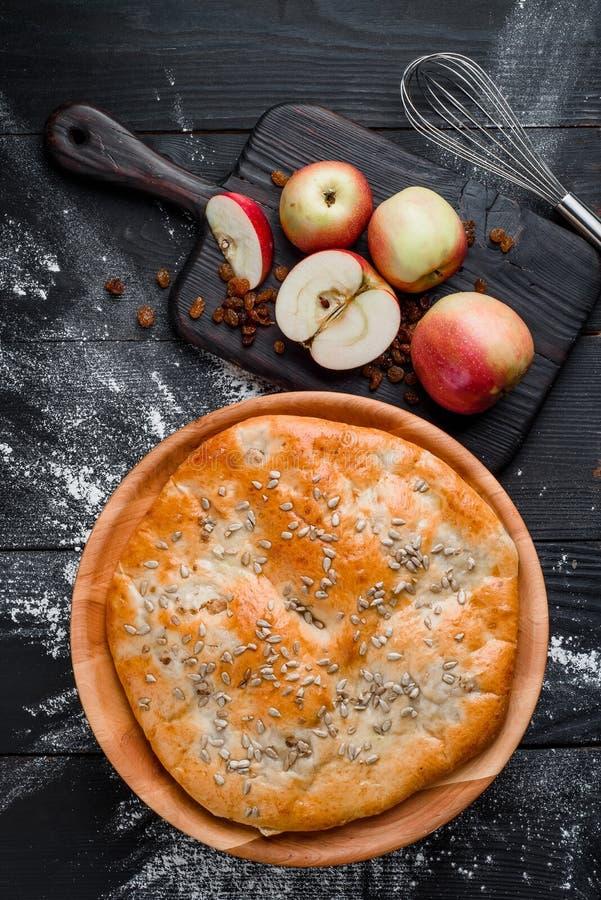 Torta di mele casalinga rotonda su un fondo di legno nero in una bella composizione Vista superiore spazio Primo piano immagine stock libera da diritti