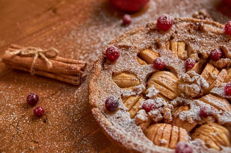 Torta di mele con i mirtilli rossi freschi e le noci decorati con cannella Appena torta di mele in polvere al forno su fondo marr fotografie stock