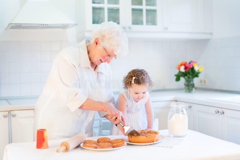 Torta di mele di cottura della nonna con la sua nipote fotografia stock libera da diritti
