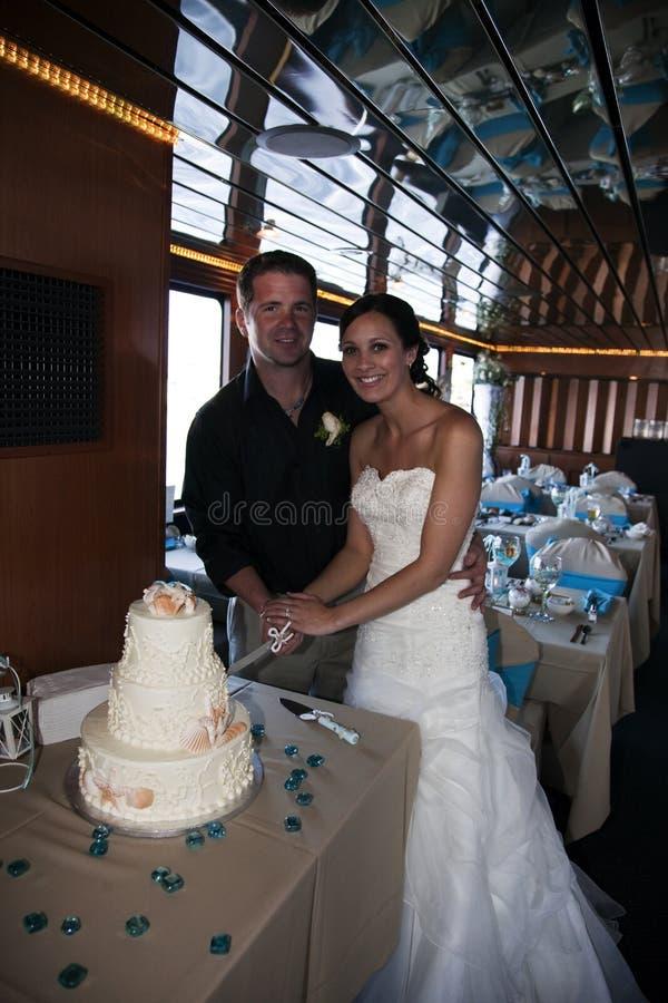 Torta di taglio dello sposo e della sposa immagine stock libera da diritti