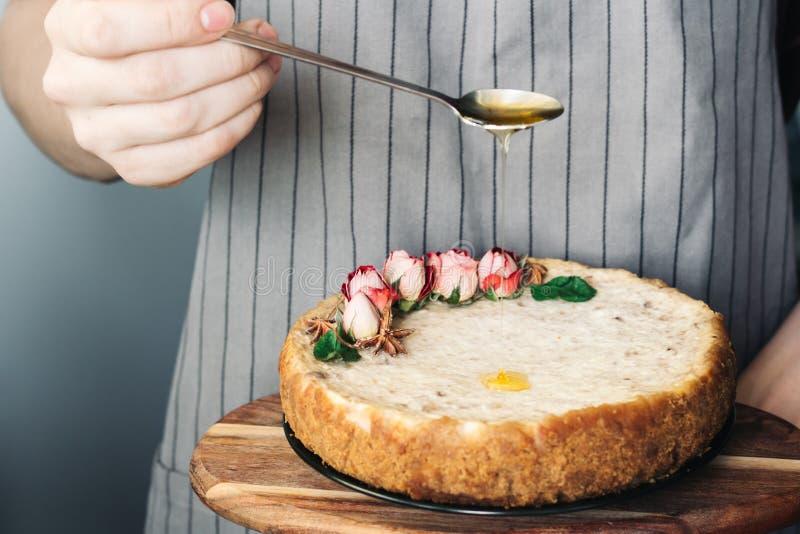 Torta do requeijão e das bananas Bolo de queijo recentemente cozido nas mãos do homem no fundo do avental sobremesa doce popular imagens de stock royalty free