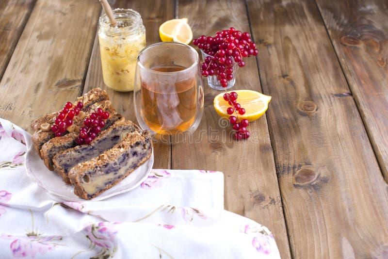 Torta doce caseiro para o café da manhã com limão e bagas do corinto preto e do corinto vermelho Um vidro do chá Fundo de madeira imagens de stock royalty free