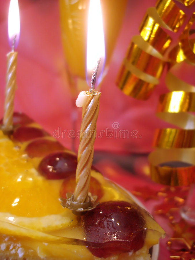 Torta e candele dorate fotografie stock