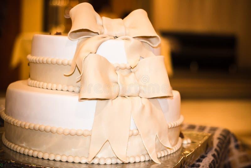 Torta elegante del oro blanco, adornada con las cintas y las gotas foto de archivo