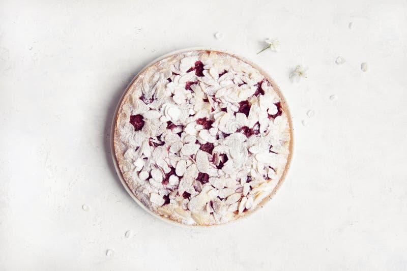 Torta entera de la cereza con los p?talos de la almendra y polvo del az?car en el fondo blanco con las flores de la cereza fotos de archivo