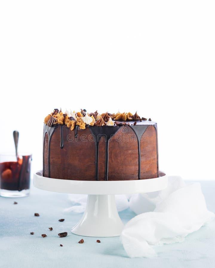 Torta fácil del goteo del cumpleaños con el ganache derretido del chocolate con la decoración del partido en un fondo blanco Copi fotos de archivo