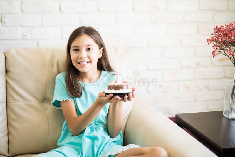 Torta feliz de la tenencia de la muchacha en casa foto de archivo libre de regalías