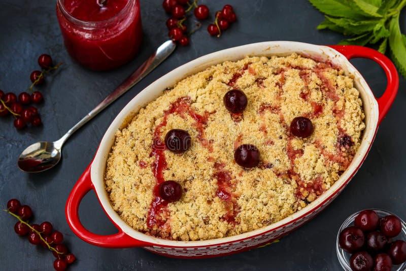 Torta fresca casalinga della briciola della ciliegia con farina integrale nella forma ceramica su un fondo scuro, pronto da mangi immagini stock libere da diritti