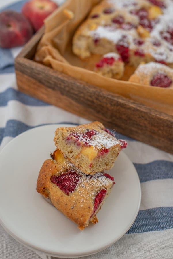 Torta hecha casera de la almendra con el melocotón y las frambuesas fotos de archivo