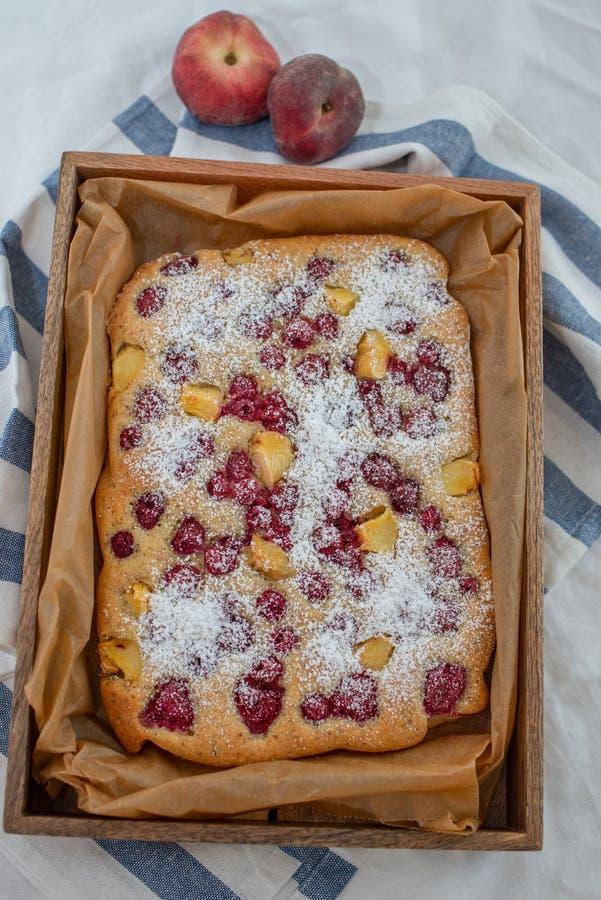 Torta hecha casera de la almendra con el melocotón y las frambuesas imagenes de archivo