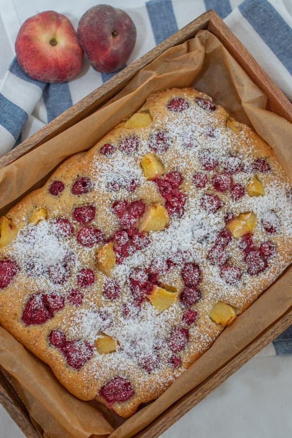 Torta hecha casera de la almendra con el melocotón y las frambuesas foto de archivo libre de regalías