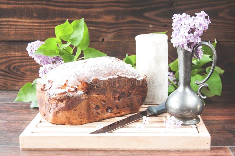 Torta hecha en casa cocida sacada el polvo con los soportes del polvo en una placa blanca cerca de las flores de la lila imagenes de archivo