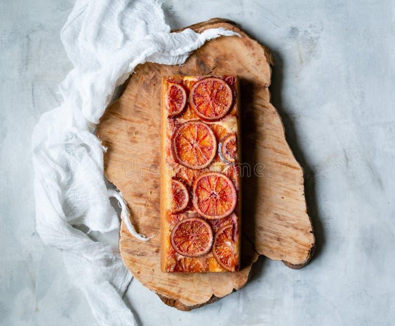 Torta hecha en casa con las naranjas de sangre encendido en un tablero de madera y un fondo gris claro Estilo escandinavo Foco se imagenes de archivo