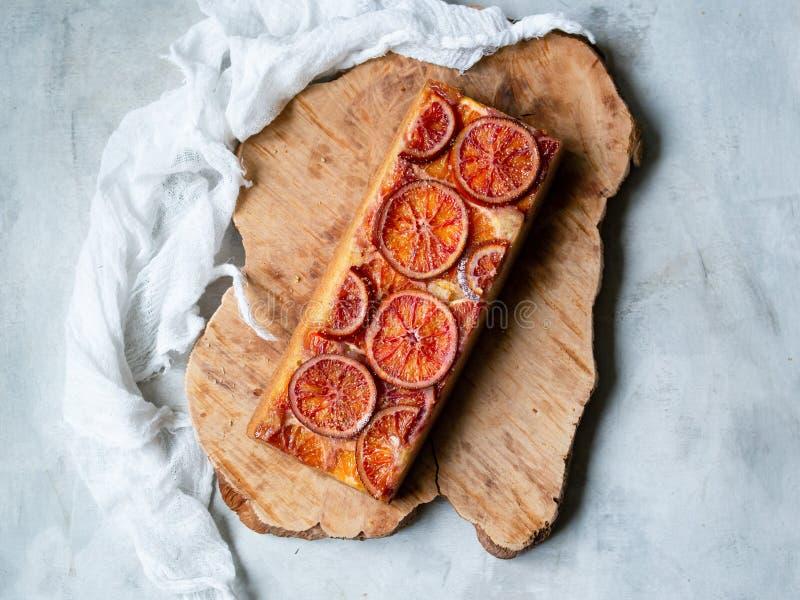 Torta hecha en casa con las naranjas de sangre encendido en un tablero de madera y un fondo gris claro Estilo escandinavo Foco se imagen de archivo libre de regalías