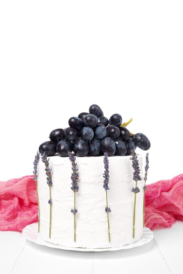 Torta hecha en casa de la crema agria adornada con las uvas y la lavanda en un fondo de madera blanco foto de archivo libre de regalías