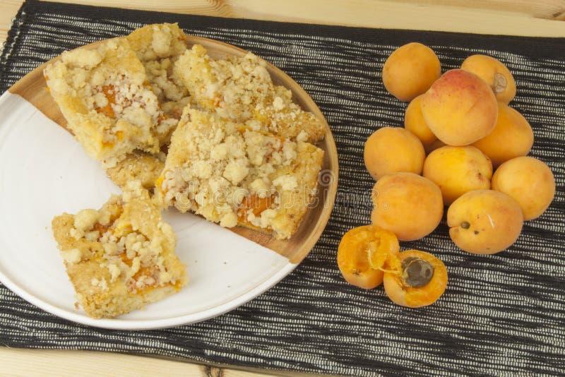 Torta hecha en casa del albaricoque en una placa Albaricoques recientemente escogidos en una tabla de madera imagen de archivo