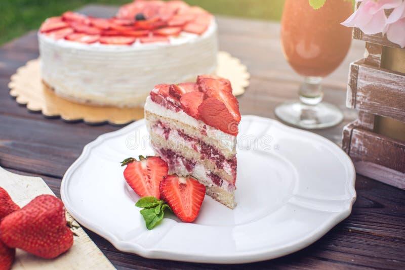 Torta hecha en casa deliciosa del verano con las fresas y la crema de la mantequilla en un pórtico de madera y un pedazo en la pl fotografía de archivo libre de regalías