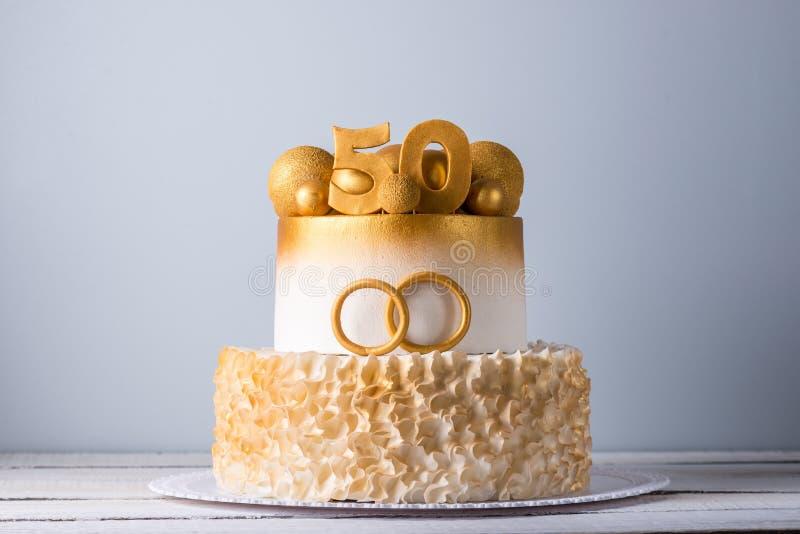 Torta hermosa para el 50.o aniversario de la boda adornada con las bolas y los anillos del oro Concepto de postres festivos imagen de archivo libre de regalías