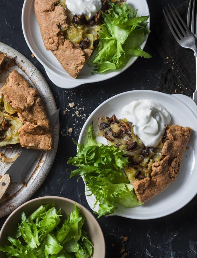 Torta inteira selvagem da grão dos cogumelos e das batatas do vegetariano rústico com iogurte grego e salada verde em um fundo es foto de stock royalty free