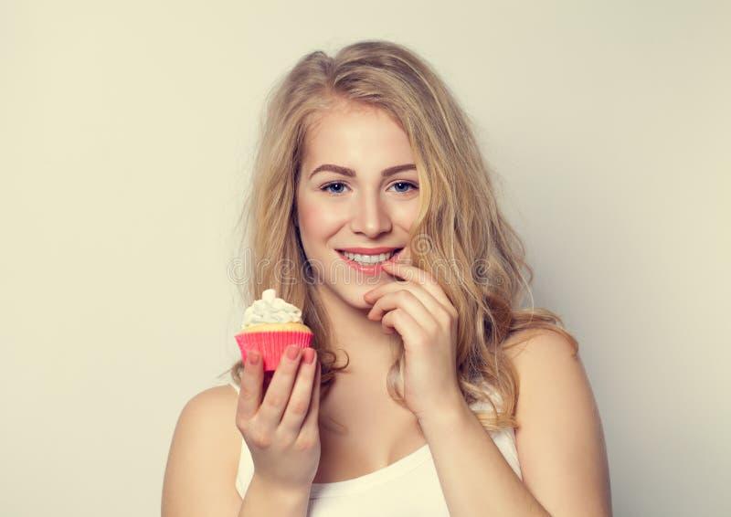 Torta linda sonriente de la tenencia de la muchacha en sus manos imagenes de archivo