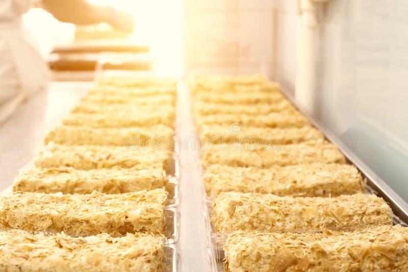 Torta Napoleon con leche condensada y pasta de hojaldre El confitero hace la torta, sol, curruscante imagen de archivo