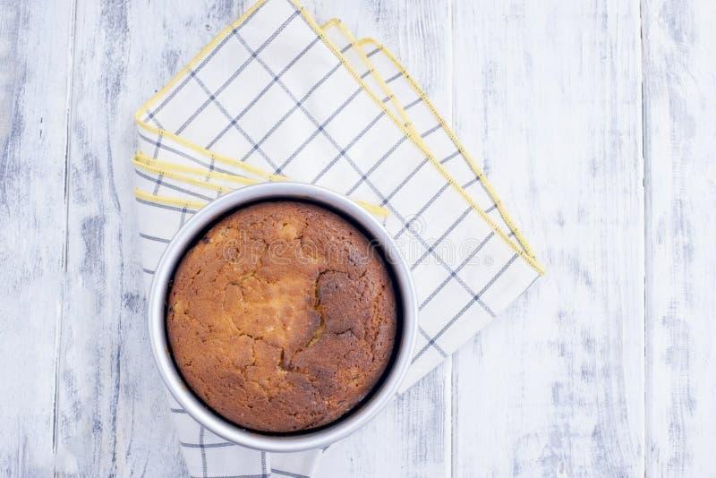 Torta no formulário redondo pronto para o bolo Na toalha de mesa em uma gaiola Em um fundo de madeira branco e em um espaço livre foto de stock royalty free