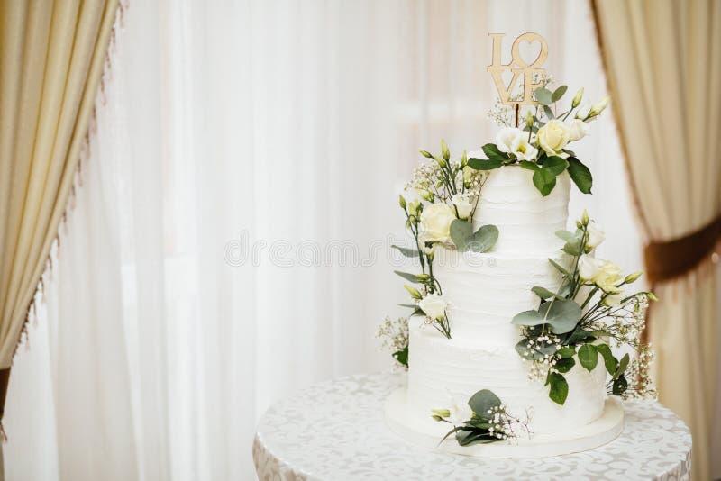 Torta nunziale bianca con i fiori L'amore di parola con cuore fotografie stock libere da diritti