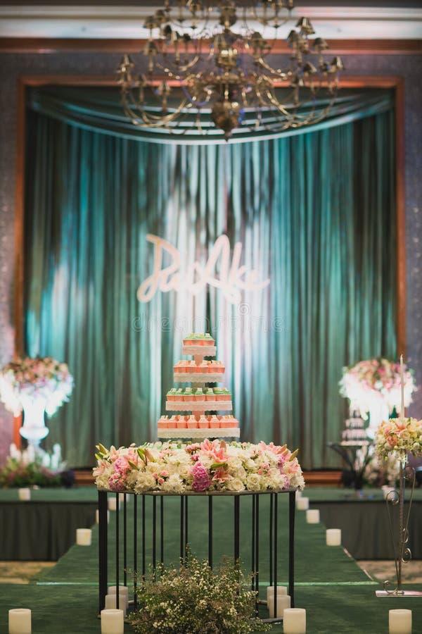 Torta nunziale bianca con il fiore Fondo variopinto dell'interno della torta nunziale bigné nella stanza della festa nuziale Bign fotografie stock libere da diritti