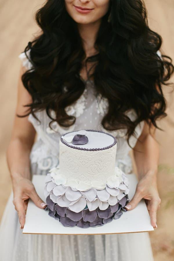 Torta nunziale creativa ed alla moda nelle mani di bella e ragazza di modello castana elegante in un vestito bianco dal pizzo immagini stock
