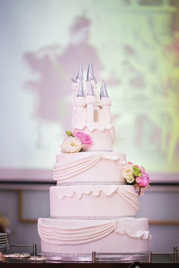 Torta nunziale decorata con i fiori e un castello immagini stock