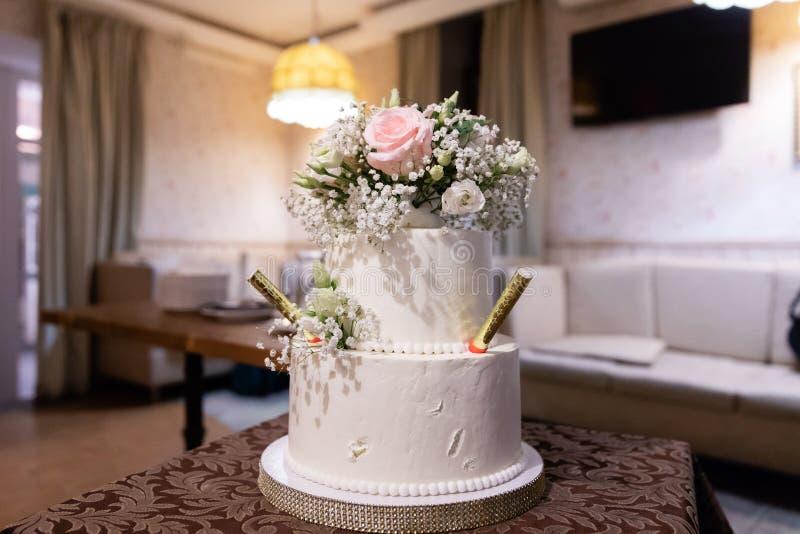 Torta nunziale decorata con i fiori sulla tavola fotografia stock libera da diritti