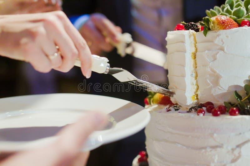 Torta nunziale del taglio dello sposo e della sposa fotografia stock
